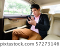 Businessman texting on smartphone in car 57273146