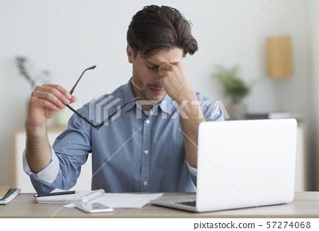 Guy Massaging Nosebridge Holding Eyeglasses Sitting At Laptop 57274068
