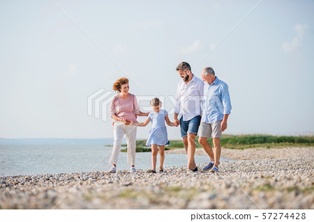 Multigeneration family on a holiday walking by the lake, holding hands. 57274428