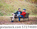 Senior father and his son sitting on bench in nature, talking. 57274689