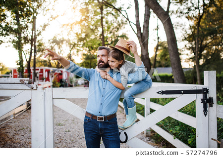 A portrait of father with small daughter outdoors on family farm. 57274796