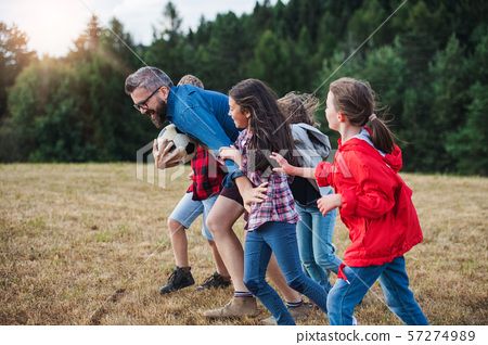 Group of school children with teacher on field trip in nature, running. 57274989
