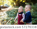 Twin toddler sibling boy and girl standing in autumn forest. Copy space. 57276338
