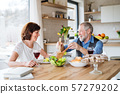 Senior couple in love having lunch indoors at home, talking. 57279202