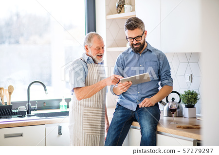 Adult hipster son and senior father indoors in kitchen at home, using tablet. 57279297