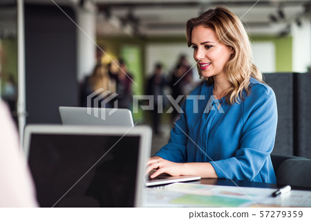 Young businesswoman with laptop sitting in an office, working. 57279359