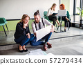 A group of young business people sitting on the floor in an office, talking. 57279434