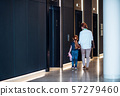 A rear view of businesswoman with small daughter walking in office building. 57279460