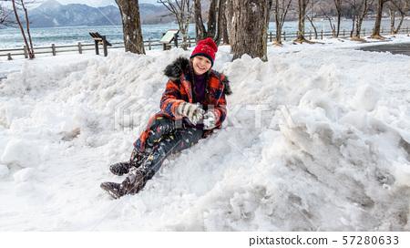 Young girl having fun in snow 57280633