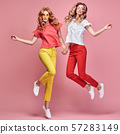 Fashion. Two happy woman laughing jump Having Fun 57283149