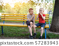 Two boys have a snack on a bench in the park and 57283943