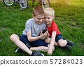 Two boys with a smartphone in their hands are 57284023