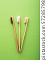 Dental care with eco friendly bamboo toothbrush on green background top view. Zero waste and plastic 57285798
