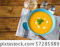 Top view of pumpkin soup with cream in blue plate 57285989