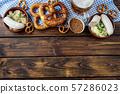 Beer mug, pretzels and sausages on wooden table. 57286023