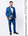 Full body shot of young handsome bearded businessman in blue suit 57292776