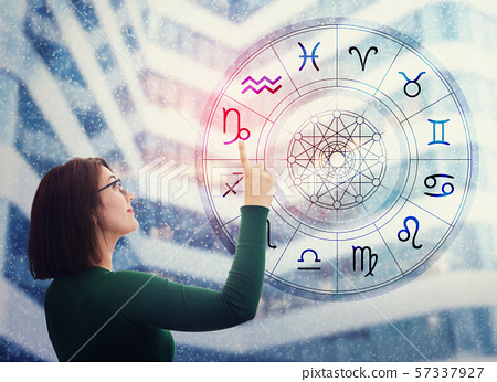 Woman choosing a zodiac sign from the astrological 57337927