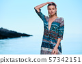 Fashionable woman posing on a beach with rocks in 57342151