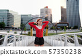 Front view of young woman runner with earphones in city, resting. 57350238