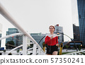 Front view of young woman runner with earphones jogging in city. 57350241