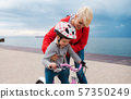 Mother helping small daughter to ride bicycle outdoors on beach. 57350249