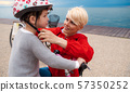 Mother and small daughter with bicycle outdoors on beach, putting on helmet. 57350252