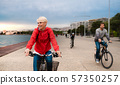 Young family riding bicycles outdoors on beach. 57350257