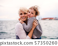 Young mother with small daughter standing outdoors on beach. 57350260