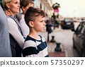 Side view of small boy with family standing outdoors in town. 57350297