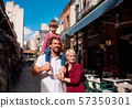 Young family with small daughter standing outdoors in town on holiday. 57350301