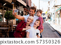 A young family with two small children standing outdoors in town, taking selfie. 57350326