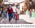 Young family with two small children walking outdoors in town on holiday. 57350356