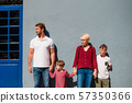 Front view of young family with two small children standing outdoors in town. 57350366