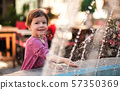 Small girl standing by water fountain outdoors in town. 57350369