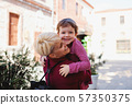 Mother with small daughter standing outdoors in mediterranean town. 57350375