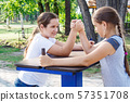 two teenage girls are engaged in arm wrestling 57351708