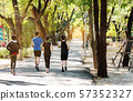 Asian runners, men and women, jogging in park 57352327