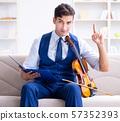 Young musician man practicing playing violin at home 57352393