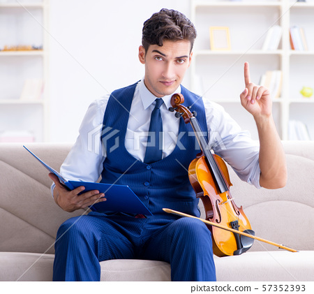 Young musician man practicing playing violin at home 57352393