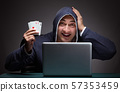 Young man wearing a hoodie sitting in front of a laptop computer 57353459