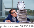 Businessman with pile stack of paper paperwork and an alarm cloc 57355136
