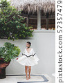 Asian woman in white light tunic, barefoot. Casual 57357479