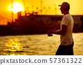Young man fishing at sea 57361322