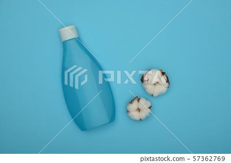 Feminine shower gel and cotton flower over blue 57362769