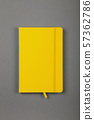 Yellow leather cover notebook over grey 57362786
