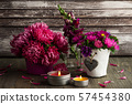 Red chrysanthemum and lit candles 57454380
