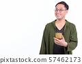 Happy Japanese man with eyeglasses thinking while using phone 57462173