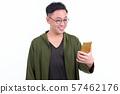 Portrait of happy Japanese man with eyeglasses using phone 57462176