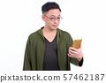 Portrait of Japanese man with eyeglasses using phone 57462187