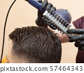 Hairstyling with round comb and hair dryer, close 57464343
